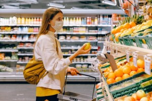 woman holding fruit and shopping basket